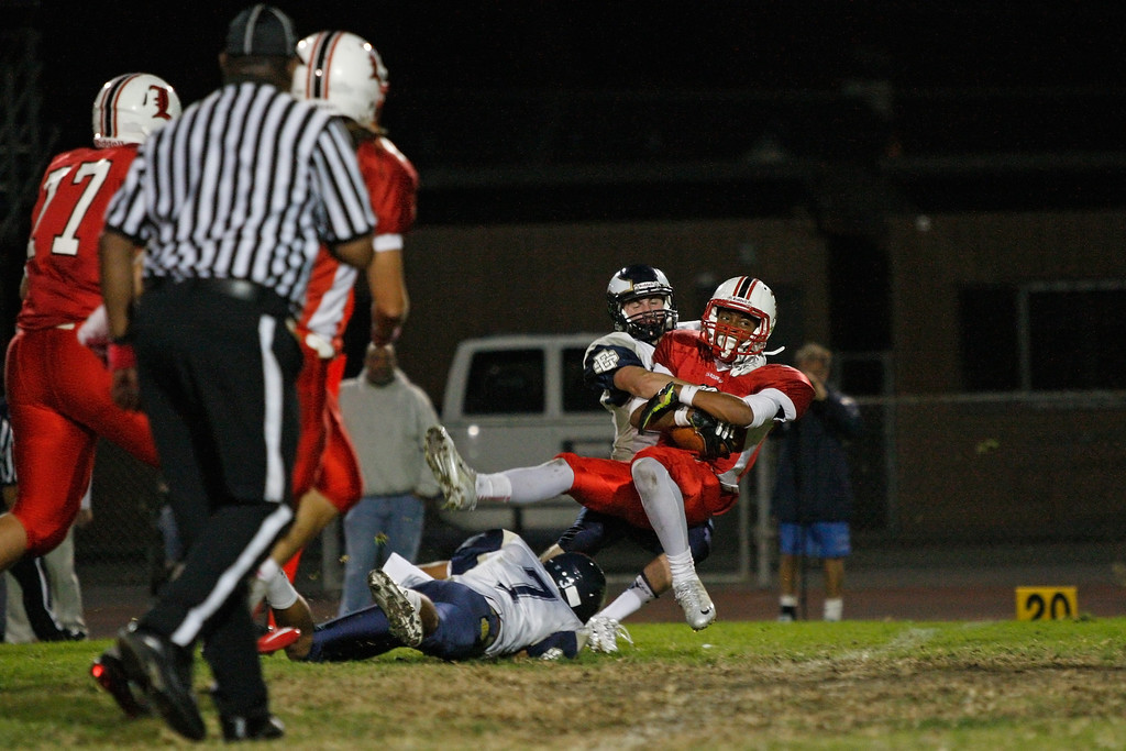 . Austin Manigo #9 of Lawndale is tackled by the defense of El Segundo in a Pioneer League matchup at Leuzinger High School on Friday, October 11, 2013 in Lawndale, Calif.  (Michael Yanow / For the Daily Breeze)