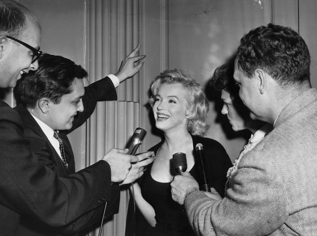 . Capturing the spotlight - Blonde actress Marilyn Monroe flashes radiant smile behind microphones of newsmen as she is questioned at #2 Sutton Place in New York City on June 21 concerning reported forthcoming marriage to playwright Arthur Miller. Marilyn confirmed report in June 20 New York newspaper story that she will wed Miller. However, the actress and the 41-year-old playwright refused to pose for pictures together at the scene of the news conference. (undated) (AP Photo)