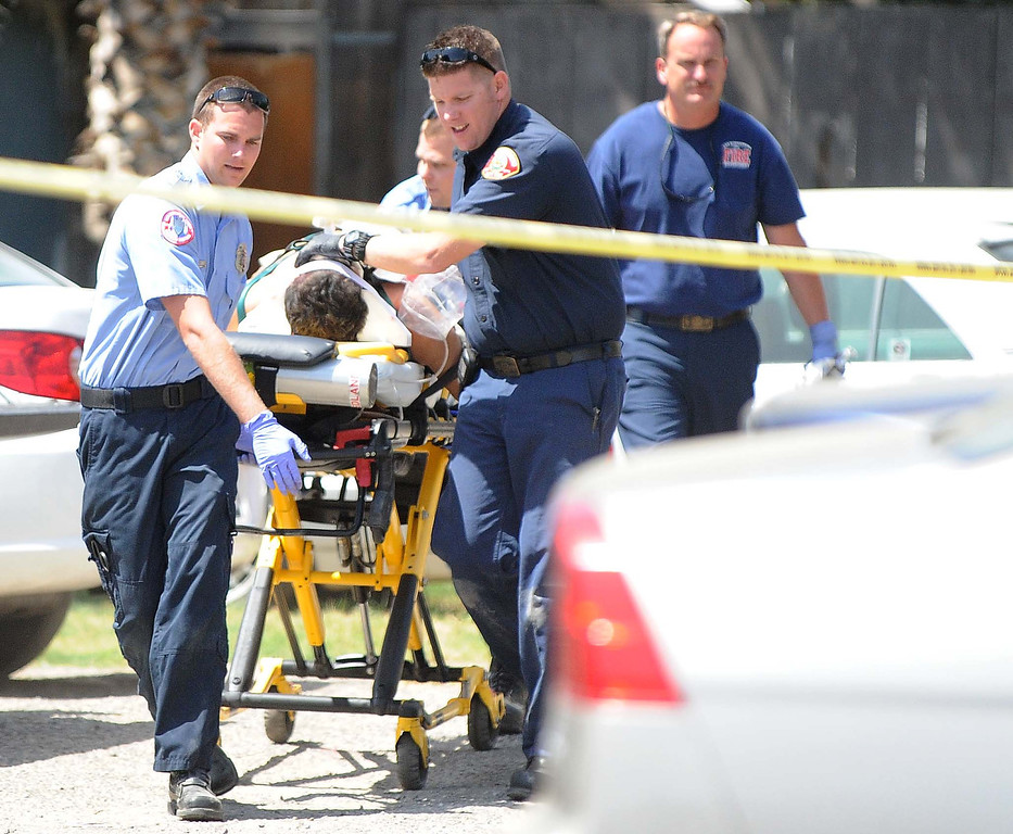 . San Bernardino City Firefighters and paramedic rush a man to a hospital after he was shot in the head Thursday May 24,2013 in the 400 block of Norman Road in San Bernardino. (Lafonzo Carter/Staff Photographer)