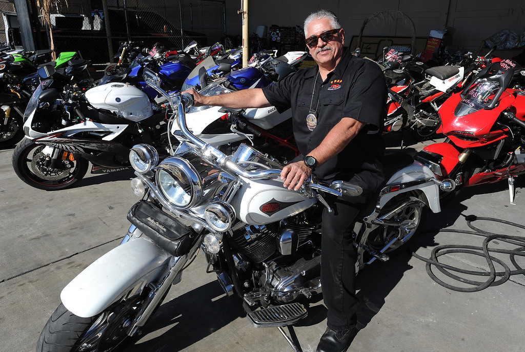 . TRAP team supervisor, Detective Jess Corral sits on a recovered stolen Harley Davidson. The Taskforce for Regional Autotheft Prevention just broke up a high-end theft/chop shop motorcycle ring. The bikes are parked in a tow yard in North Hollywood, CA. 12/20/2013, photo by (John McCoy/Los Angeles Daily News)