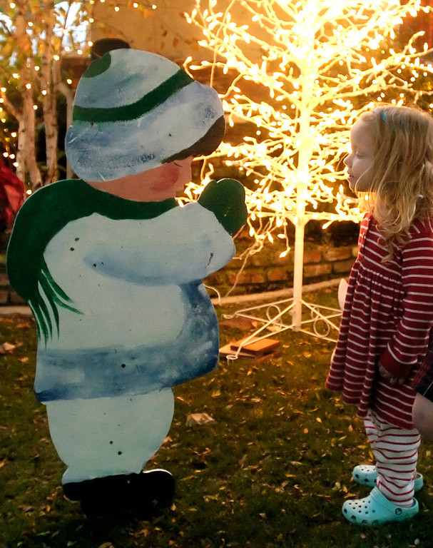 . Audrey Szalla(cq),2, checks out wood cut out of a child at her neighbor\'s Christmas display on Carol Drive in Torrance. The Sleepy Hollow neighborhood is popular destination for viewing holiday lights and displays. Nov. 26, 2007(Staff Photo by Sean Hiller)