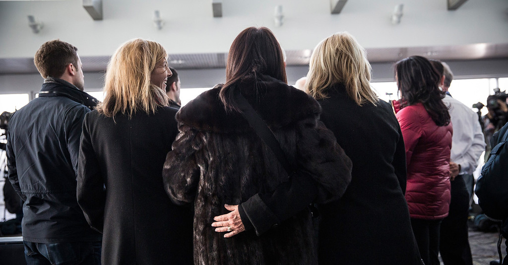 """. NEW YORK, NY - JANUARY 15:  Passengers from US Airways Flight 1549, hold each other during a press conference celebrating the five year anniversary of \""""The Miracle on the Hudson,\"""" in which a commercial jet was landed on the Hudson river on January 15, 2014 in New York City. On January 15, 2009, Chesley \""""Sully\"""" Sullenberger took off from La Guardia airport piloting US Airways Flight 1549 with 150 passengers and five crew members. The plane hit a goose shortly after take off, forcing Sullenberger to land the plane in the Hudson River; no one was killed.  (Photo by Andrew Burton/Getty Images)"""