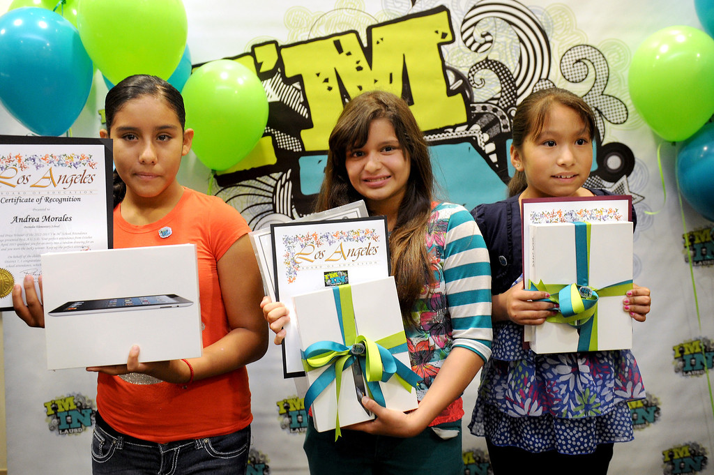 . Elementary school students Andrea Morales, left, Jasmine Vallejo, center, and Elizabeth Rios-Gomez of Canterbury Elementary hold iPads they were awarded at LAUSD headquarters, Thursday, June 13, 2013, for perfect attendance for the 2012-13 school year. (Michael Owen Baker/Staff Photographer)