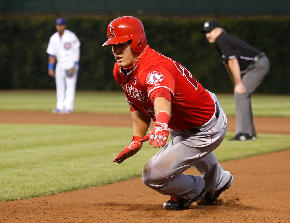 . Los Angeles Angels\' Mike Trout dives back to first to avoid the pick off by Chicago Cubs starting pitcher Jeff Samardzija during the fifth inning of an interleague baseball game Wednesday, July 10, 2013, in Chicago. (AP Photo/Charles Rex Arbogast)