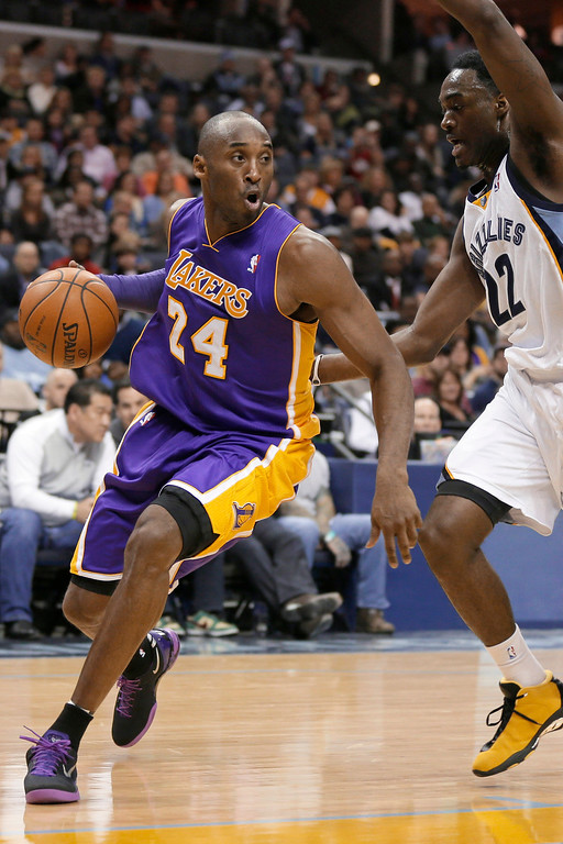 . Los Angeles Lakers\' Kobe Bryant (24) dribbles around Memphis Grizzlies\' Jamaal Franklin (22) during the first half of an NBA basketball game in Memphis, Tenn., Tuesday, Dec. 17, 2013. (AP Photo/Danny Johnston)