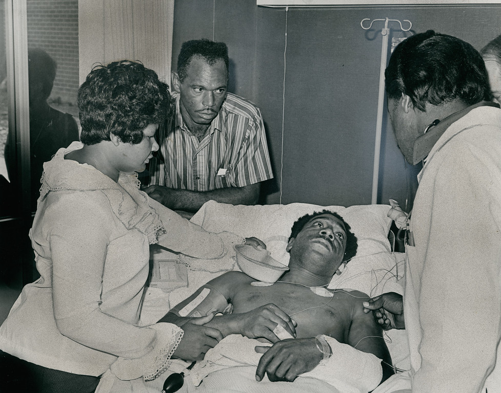 . File Photo June 25, 1971-Only known survivor of eplosion that rocked Metropolitan Water District tunnel early yesterday morning, Ralph Brissette is observed by attendant at Pacoima Memorial Lutheran Hospital. From left are his sister-in-law Bernice, brother Douglas Jr., Brissette and attendant.