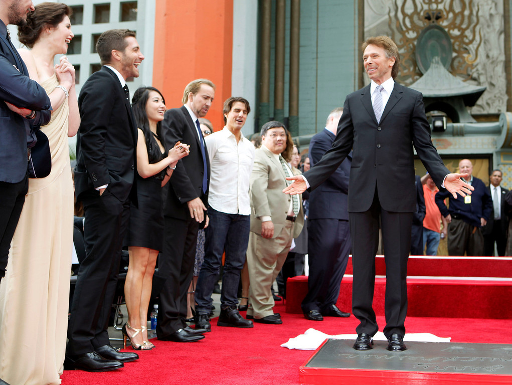 ". Movie and television producer Jerry Bruckheimer adds his hand and footprints to some 200 other celebrity impressions in the forecourt of Grauman\'s Chinese Theatre, joined by, from left, Gemma Arterton and Jake Gyllenhaal, who star in his new movie, ""The Prince of Persis The Sands of Time,\"" Alice Kim and her husband Nicolas Cage, and Tom Cruise, in the Hollywood district of Los Angeles Monday, May 17, 2010. The ceremony comes 11 days before the release of Bruckheimer\'s latest film, \""Prince of Persia: The Sands of Time.\""  Bruckheimer\'s films have earned worldwide revenues of more than $15 billion in box office, home entertainment and music receipts and have garnered 41 Academy Award nominations and six Oscars. (AP Photo/Reed Saxon)"