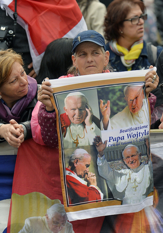 . Pilgrim hold images of Pope John Paul II, that will be canonized next Sunday, prior to the arrival of Pope Francis for his weekly general audience in St Peter\'s square at the Vatican on April 23, 2014.              (ANDREAS SOLARO/AFP/Getty Images)