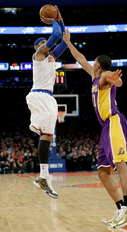 . New York Knicks\' Carmelo Anthony, left, shoots over Los Angeles Lakers\' Wesley Johnson during the second half of an NBA basketball game at Madison Square Garden, Sunday, Jan. 26, 2014, in New York. The Knicks defeated the Lakers 110-103. (AP Photo/Seth Wenig)