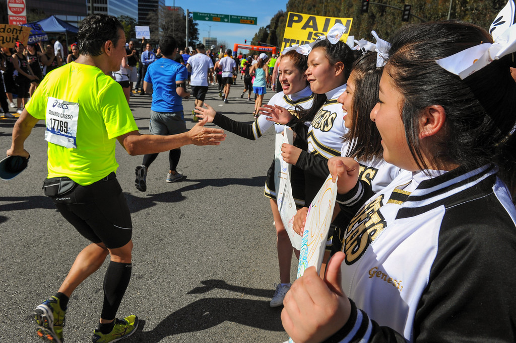 . Cheerleaders from San Fernando High School slap hands with runners on Santa Monica Boulevard in Century City during the Los Angeles Marathon, Sunday, March 9, 2014. (Photo by Michael Owen Baker/L.A. Daily News)