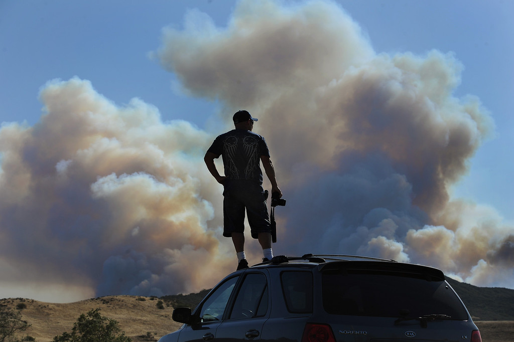 . Matt Moore stands on the roof of his car while watching smoke rise from the Springs fire in Sycamore Canyon Thursday, May 2, 2013. (Michael Owen Baker/Los Angeles Daily News)