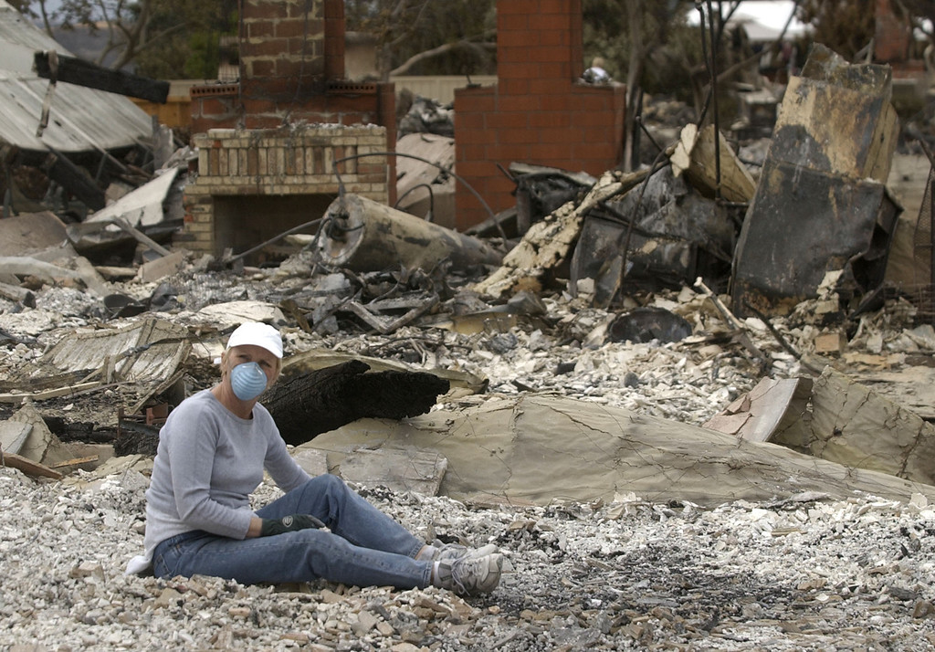 . Cathy Flanders pauses while sorting through rubble of a friend\'s house which was burned in Scripps Ranch area of San Diego, Calif. Thursday, Oct. 30, 2003. The home was among more than 1,500 lost in the 275,000 acre Cedar fire. (AP Photo/Charlie Riedel)