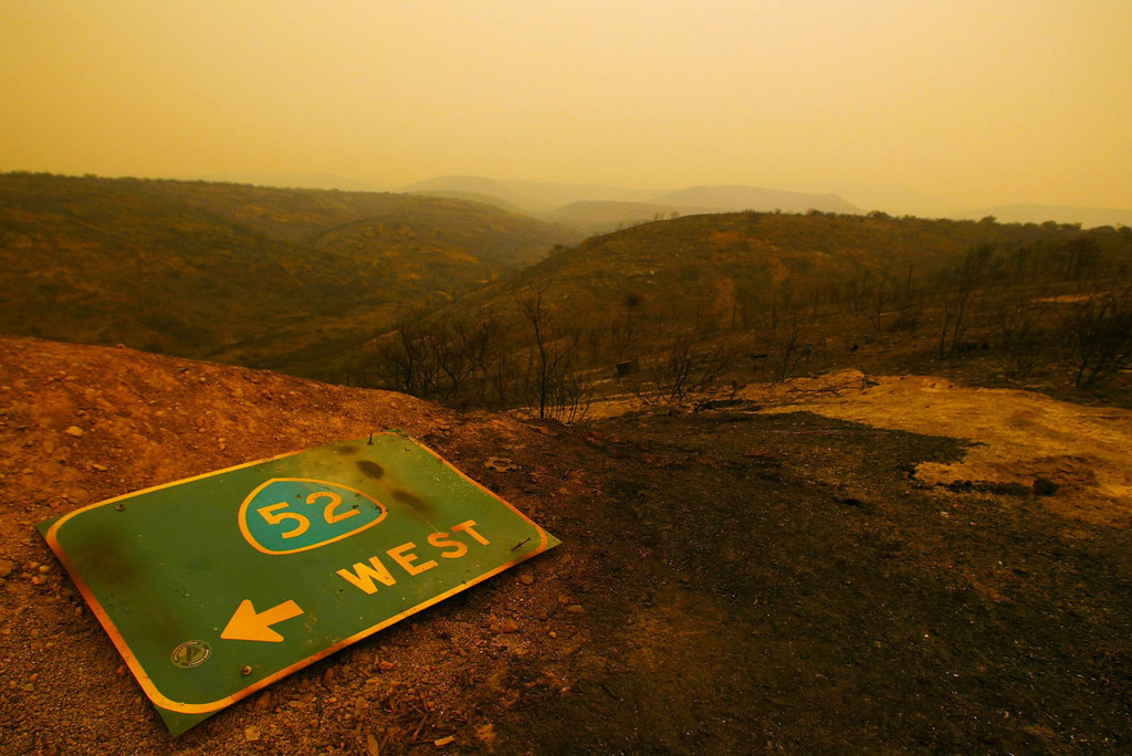 . SAN DIEGO - OCTOBER 27:  A sign for the 52 freeway lies among the hills charred by the Cedar Fire October 27, 2003 near Lakeside in San Diego, California. The death toll stands at 13, with more than 1,000 homes being reduced to ashes as southern California fires continue to burn. Winds have eased a bit, but 30,000 homes remain threatened by the fires, which have charred more than 400,000 acres, according to officials. Davis, who has activated the National Guard, predicted damages will be in the billions of dollars.  (Photo by Donald Miralle/Getty Images)