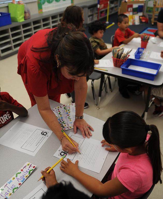 . Kindergarten teacher Maria Doyle,helps a student with her work Tuesday August 9, 2013 at Little Mountain Elementary School in San Bernardino.LaFonzo Carter/ Staff Photographer