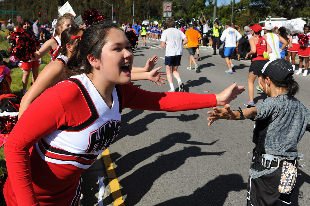 . Cheerleaders from Huntington Middle School slap hands with runners on Santa Monica Boulevard in Century City during the Los Angeles Marathon, Sunday, March 9, 2014. (Photo by Michael Owen Baker/L.A. Daily News)