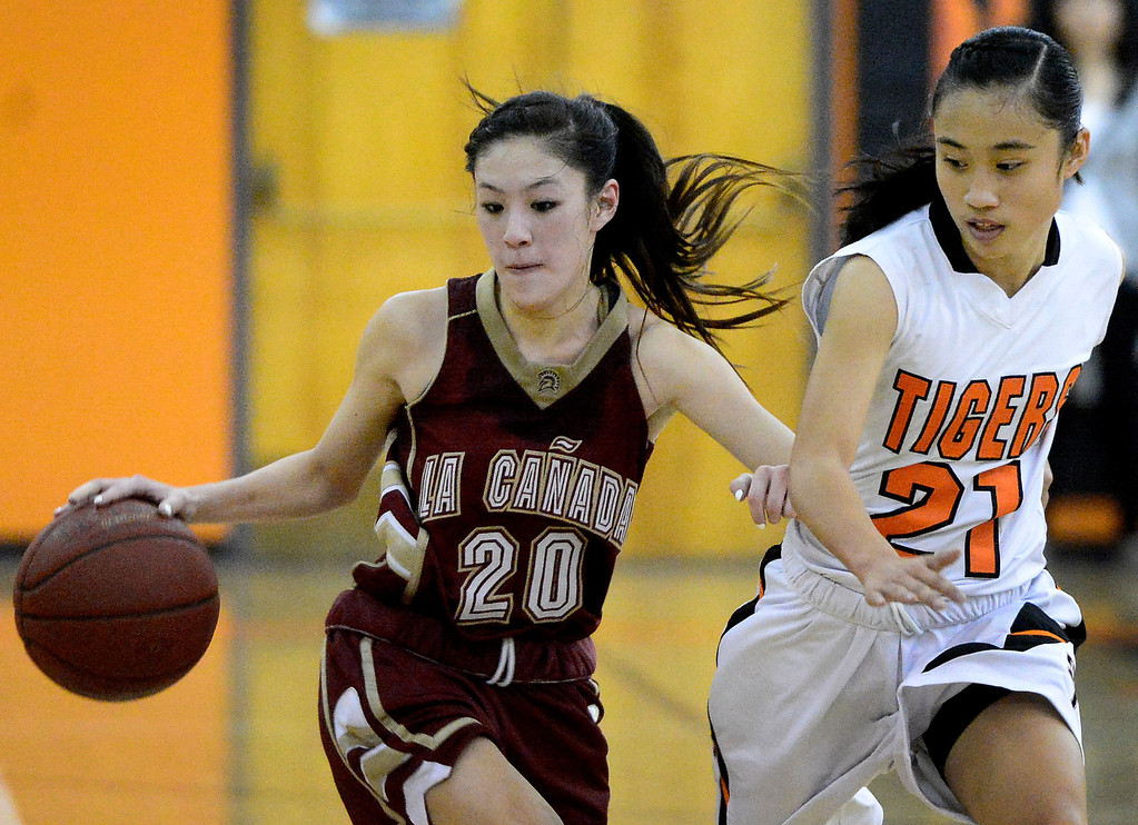 . La Canada\'s Courtney Chen (20) drives the ball as South Pasadena\'s Jalynne Li (21) approaches during South Pasadena\'s 66-58 win Friday night, January 31, 2014 at South Pasadena High School. (Photo by Sarah Reingewirtz/Pasadena Star-News)