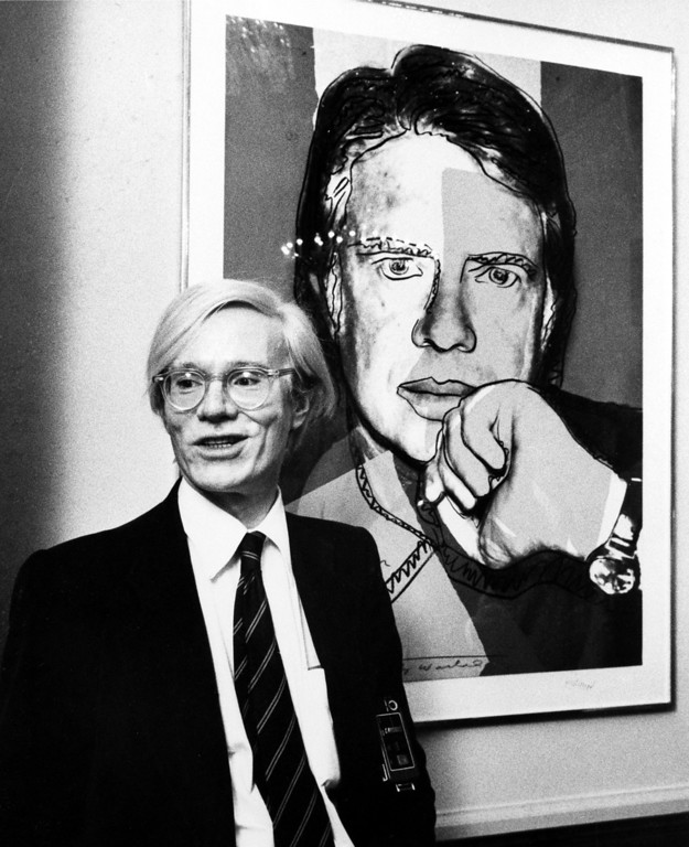 ". Pop artist Andy Warhol poses next to his painting, ""Jimmy Carter 76,\"" at a reception on Capitol Hill in Washington, D.C., on June 14, 1977.  The work is part of a collection titled \""Inaugural Impressions\"" on display in the offices of the House Administration Committee.  (AP Photo)"