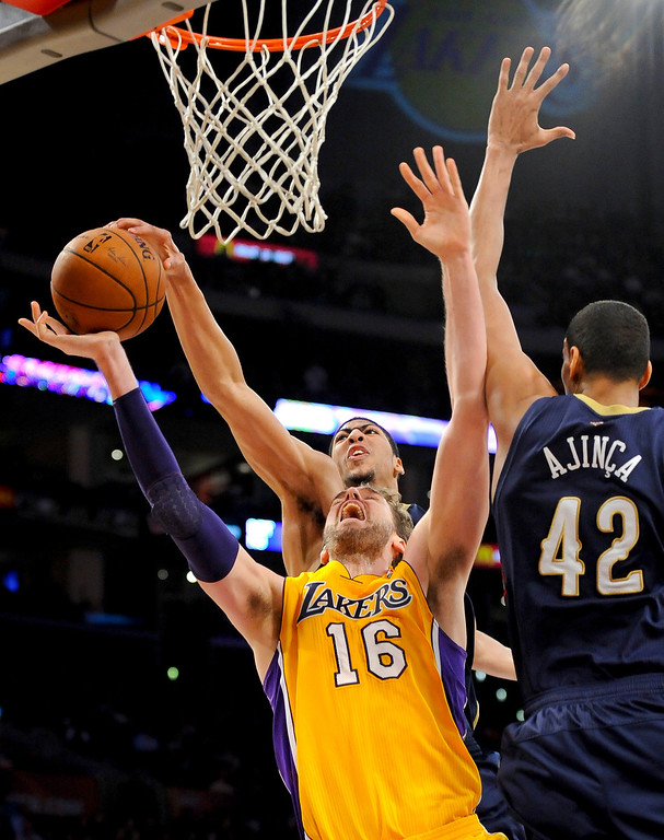 . New Orleans Pelicans forward Anthony Davis, back center, blocks Los Angeles Lakers center Pau Gasol (16), of Spain, shot as center Alexis Ajinca (42), of France, helps out in the second half of an NBA basketball game, Tuesday, March 4, 2014, in Los Angeles. The Pelicans won 132 to 125. (AP Photo/Gus Ruelas)