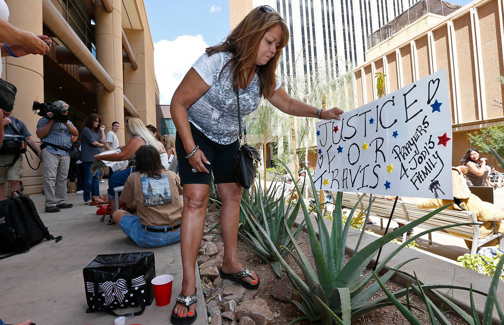 . Carol Peifer, of Glendale, Ariz., places a sign in front of Maricopa County Superior Court as she and dozens of other spectators wait for a verdict in the Jodi Arias murder trial, Tuesday, May 7, 2013, in Phoenix.  A Phoenix jury is on its third day of deliberations in the trial of Jodi Arias, who is accused of murdering her one-time boyfriend Travis Alexander, in Arizona. (AP Photo/Ross D. Franklin)