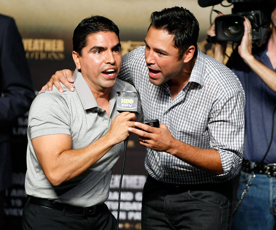 ". LAS VEGAS - SEPTEMBER 18:  Radio personality Eddie ""Piolin\"" Sotelo (L) and boxing promoter Oscar De La Hoya entertain the crowd during the official weigh-in for boxers Floyd Mayweather Jr. and Juan Manuel Marquez at the MGM Grand Garden Arena September 18, 2009 in Las Vegas, Nevada. The two will fight at the MGM on September 19.  (Photo by Ethan Miller/Getty Images)"