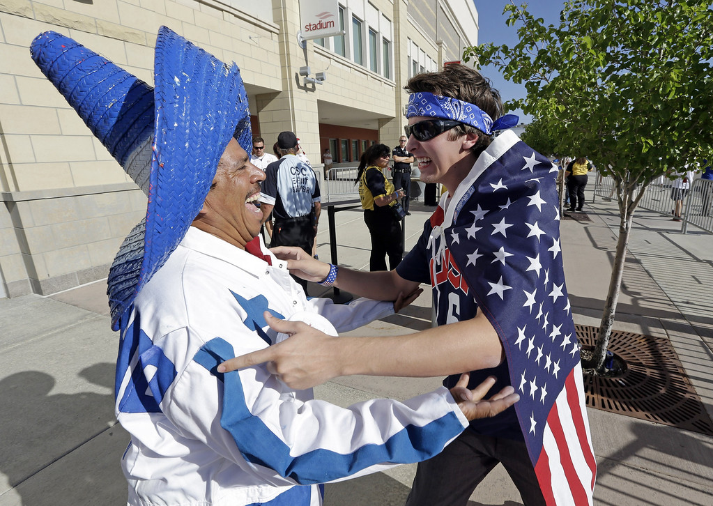 . U.S. soccer fan Kyle Flowers, right, and Honduras fan Harly Redondo, left, celebrate before the start an World Cup qualifying soccer match between Honduras and the U.S. at Rio Tinto Stadium on Tuesday, June 18, 2013, in Sandy, Utah.  (AP Photo/Rick Bowmer)