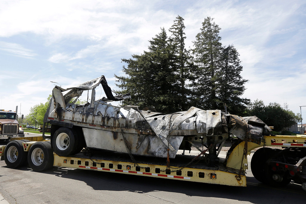 . The demolished remains of a FedEx truck is towed into a CalTrans maintenance station in Willows, Calif., Friday, April 11, 2014. At least ten people were killed and dozens injured in the fiery crash on Thursday, April 10, between a FedEx truck and a bus carrying high school students on a visit to a Northern California college. (AP Photo/Jeff Chiu)