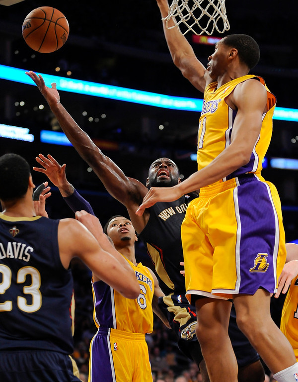 . New Orleans Pelicans forward Tyreke Evans, center, drifts between Los Angeles Lakers guard Kent Bazemore (6) and forward Wesley Johnson, right front, for a basket in the first half of an NBA basketball game, Tuesday, March 4, 2014, in Los Angeles.(AP Photo/Gus Ruelas)