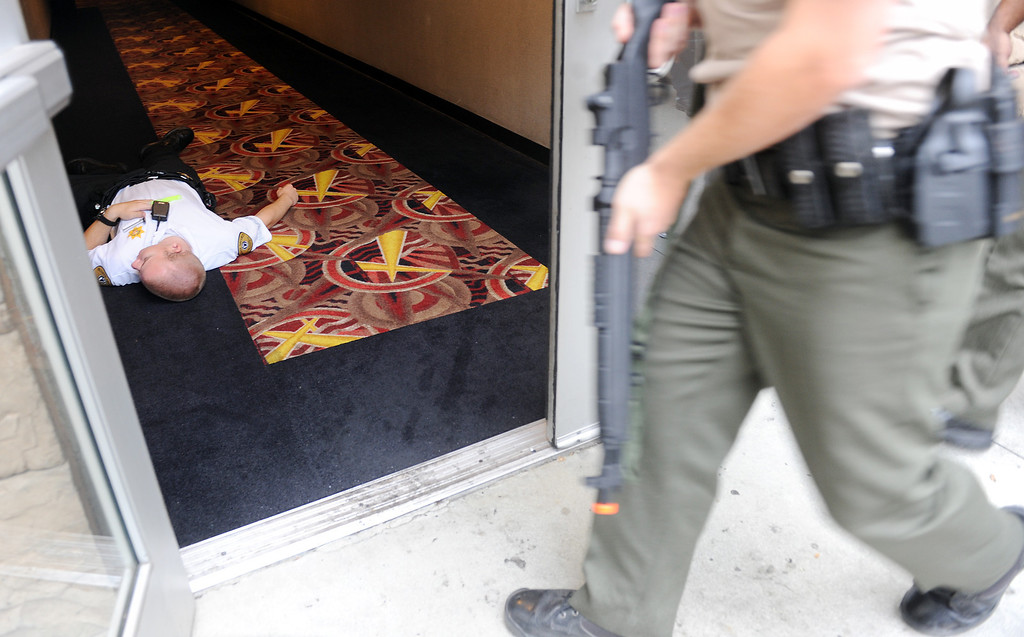 . (Will Lester/Inland Valley Daily Bulletin) Rancho Cucamonga Sheriff deputy enters a side entrance to a movie theater as a victim lies on the ground during a mock theater shooting training drill Thursday morning August 1, 2013 at Victoria Gardens in Rancho Cucamonga.