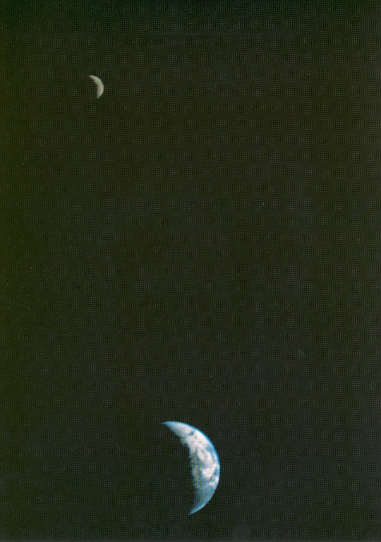 . This picture of the Earth and Moon in a single frame, the first of its kind ever taken by a spacecraft, was recorded September 18, 1977, but NASAs Voyager 1 when it was 7.25 million miles (11.66 million kilometers) from Earth.  The moon is at the top of the picture and beyond the Earth as viewed by Voyager. In the picture are eastern Asia, the western Pacific Ocean and part of the Arctic. Voyager 1 was directly above Mt. Everest (on the night side of the planet at 25 degrees north latitude) when the picture was taken.  The photo was made from three images taken through color filters, then processed by the Image Processing Lab at Jet Propulsion Laboratory (JPL). Because the Earth is many times brighter than the Moon, the Moon was artificially brightened by a factor of three relative to the Earth by computer enhancement so that both bodies would show clearly in the prints.  Voyager 1 was launched September 5, 1977 and Voyager 2 on August 20, 1977. JPL is responsible for the Voyager mission.  *Image Credit*: NASA  NASA Identifier: SPD-SLRSY-1643