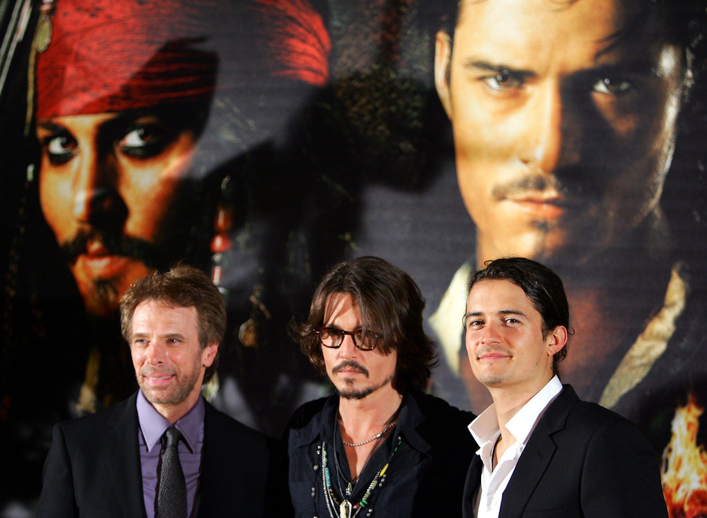 """. U.S. actor Johnny Depp, center, U.S. film producer Jerry Bruckheimer, left, and British actor Orlando Bloom attend the screening for the French premiere of their latest movie \""""Pirates of the Caribean: Dead Man\'s Chest,\"""" in Paris, Thursday July 6, 2006.  (AP Photo/Remy de la Mauviniere)"""