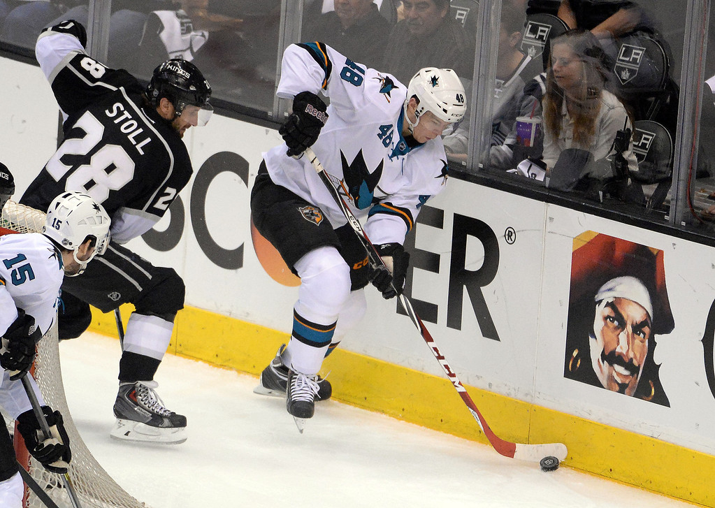 . San Jose Sharks center Tomas Hertl (48) controls the puck against the boards past Los Angeles Kings center Jarret Stoll (28) as left wing James Sheppard (15) looks on during the first period in Game 4 of an NHL hockey first-round playoff series at Staples Center in Los Angeles on Thursday, April, 24  2014.  (Keith Birmingham Pasadena Star-News)