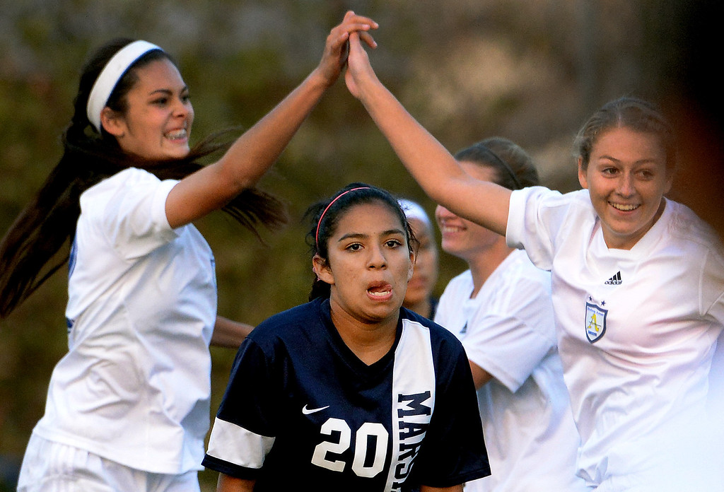. Marshall\'s Vanessa Flores (20) looks away as Bishop Amat\'s Jamie Peters, left, high fives teammate Madisyn Rodriguez after scoring in the second half of a prep soccer match at Bishop Amat High School in La Puente, Calif., on Thursday, Jan. 9, 2014.Amat won 3-0. (Keith Birmingham Pasadena Star-News)