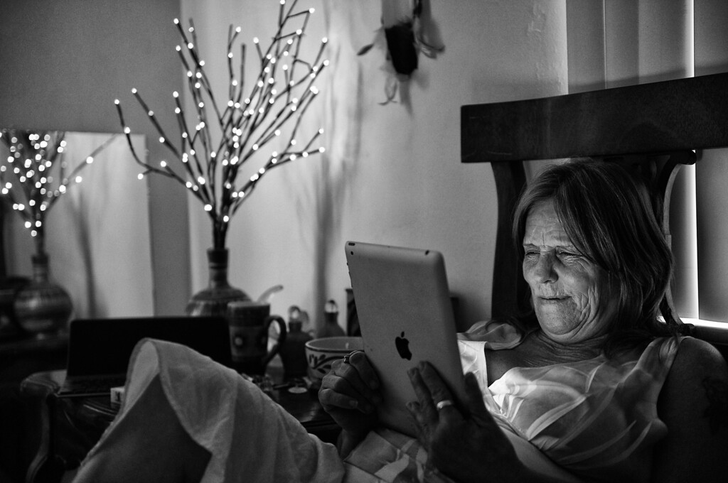 . Dorothy reads on her iPad, which she uses to reconnect with the world and for her writings and drug recovery work.