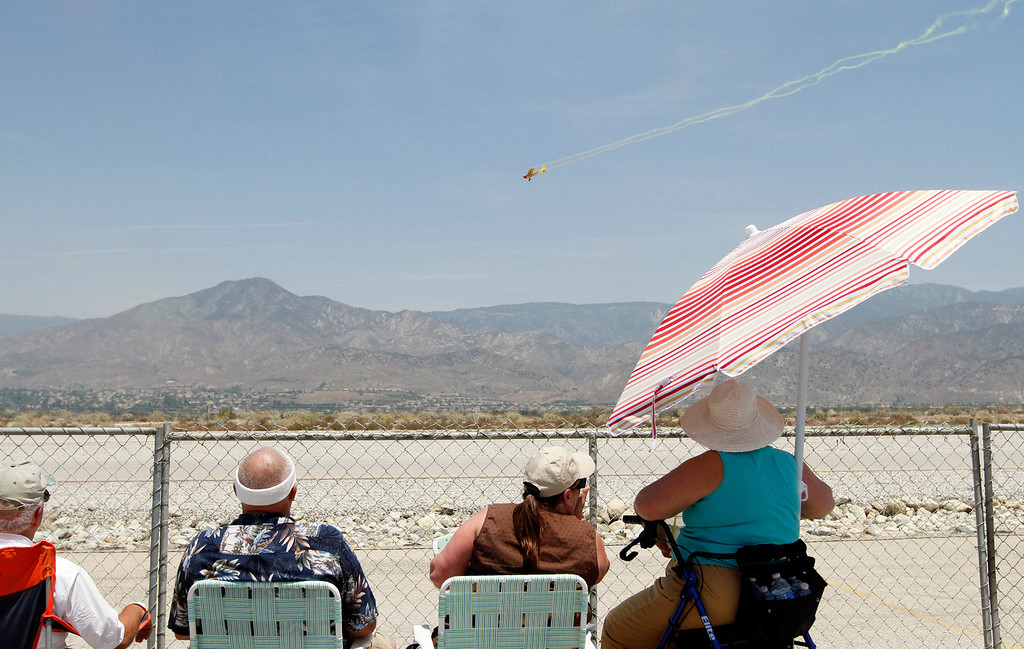 . AirFest attendees watch as Kent Pietsch gives an aerial performance in an Interstate Cadet aircraft during the Hangar 24 AirFest and 6th Anniversary Celebration on Saturday, May 17, 2014 at the Redlands Municipal Airport in Redlands, Ca. (Photo by Micah Escamilla/Redlands Daily Facts)