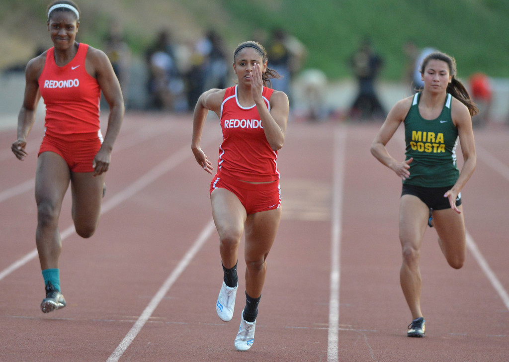 . 05-03-2013-(LANG Staff Photo by Sean Hiller)-  The Bay League track and field finals Friday night at Mira Costa High School. Redondo\'s Shelby Bassman, center, wins the girls varsity 100 meter dash.