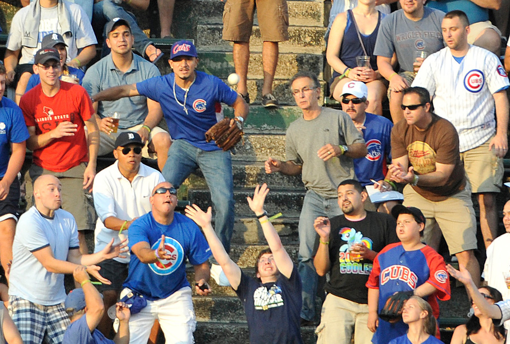 . CHICAGO, IL - JULY 10: Fans try to catch a homer off the bat  of Josh Hamilton #32 of the Los Angeles Angels of Anaheim against the Chicago Cubs during the first inning on July 10, 2013 at Wrigley Field in Chicago, Illinois. (Photo by David Banks/Getty Images)