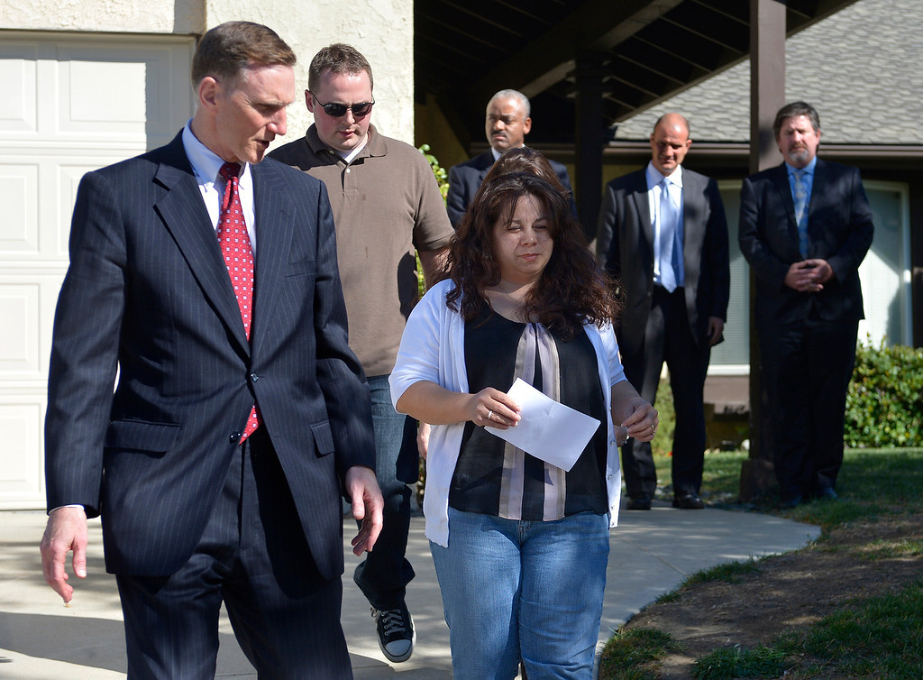 . TSA Administrator John Pistole walks with Ana Hernandez before she spoke to the media. Hernandez held a press conference on the front lawn of her home the day after her husband, TSA Behavior Detection Officer Gerardo Hernandez, was killed by a gunman in Terminal 3 at Los Angeles International Airport. Los Angeles, CA. 11/2/2013. photo by (John McCoy/Los Angeles Daily News)