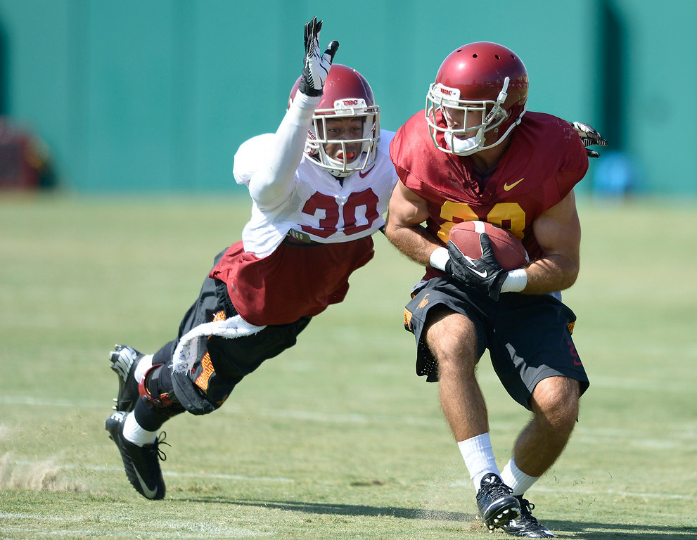 . D.J. Morgan dives to tackle Christian Tober after he caught the ball. Football practice is in full swing on the Howard Jones Field at USC. Los Angeles, CA. 8/6/2014(Photo by John McCoy Daily News)
