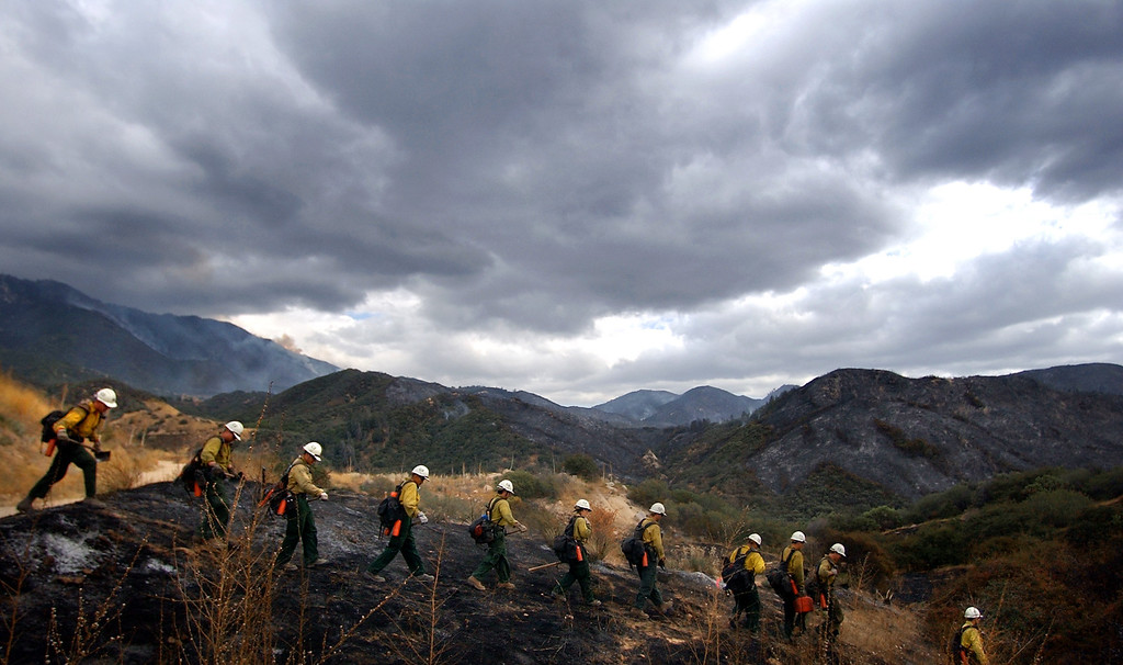 """. Ten years ago this month the arson caused Old Fire, fanned by Santa Ana winds burned thousands of acres, destroyed hundreds of homes and caused six deaths. The fire burned homes in San Bernardino, Highland, Cedar Glen, Crestline, Running Springs and Lake Arrowhead and forced the evacuation of thousand of residents. U.S. Forrest Service\'s Dalton Hotshots of Glendora head out into the burned forest to work on containing the fire with hand tools and chain saws during the \""""Old Fire\"""" in Running Springs, area Friday, Oct. 31st 2003.  (Staff file photo/The Sun)"""