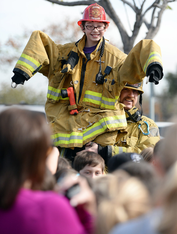. Valle Vista Elementary School fifth grader Hayden Pestel, 10, is lifted up by Rancho Cucamonga firefighter Nick Maksimuk after Pestel was recognized as a hero Tuesday February 11, 2014 by the Rancho Cucamonga fire department at the school. Pestel awoke his sleeping grandfather Thursday night after the laundry room in his home caught fire allowing them both to escape the fire without injury. Damage to the home was set at $230,000. (Will Lester/Inland Valley Daily Bulletin)