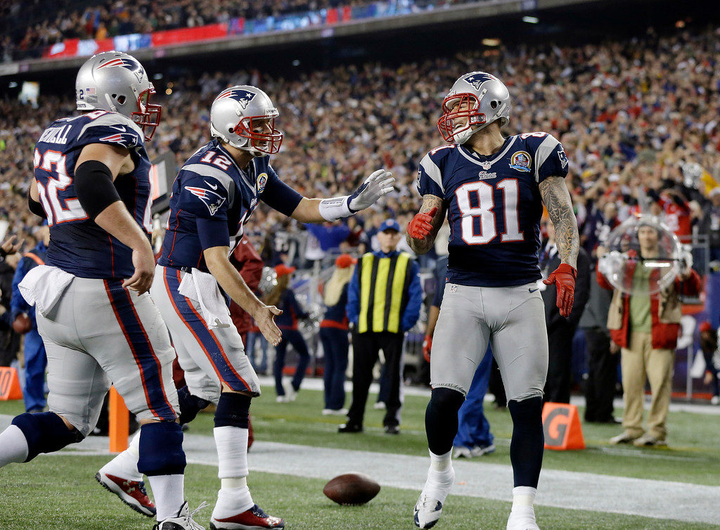 . New England Patriots quarterback Tom Brady (12) and center Ryan Wendell (62) congratulate New England Patriots tight end Aaron Hernandez (81) after his touchdown catch against the Houston Texans during the second quarter of an NFL football game in Foxborough, Mass., Monday, Dec. 10, 2012. (AP Photo/Elise Amendola)