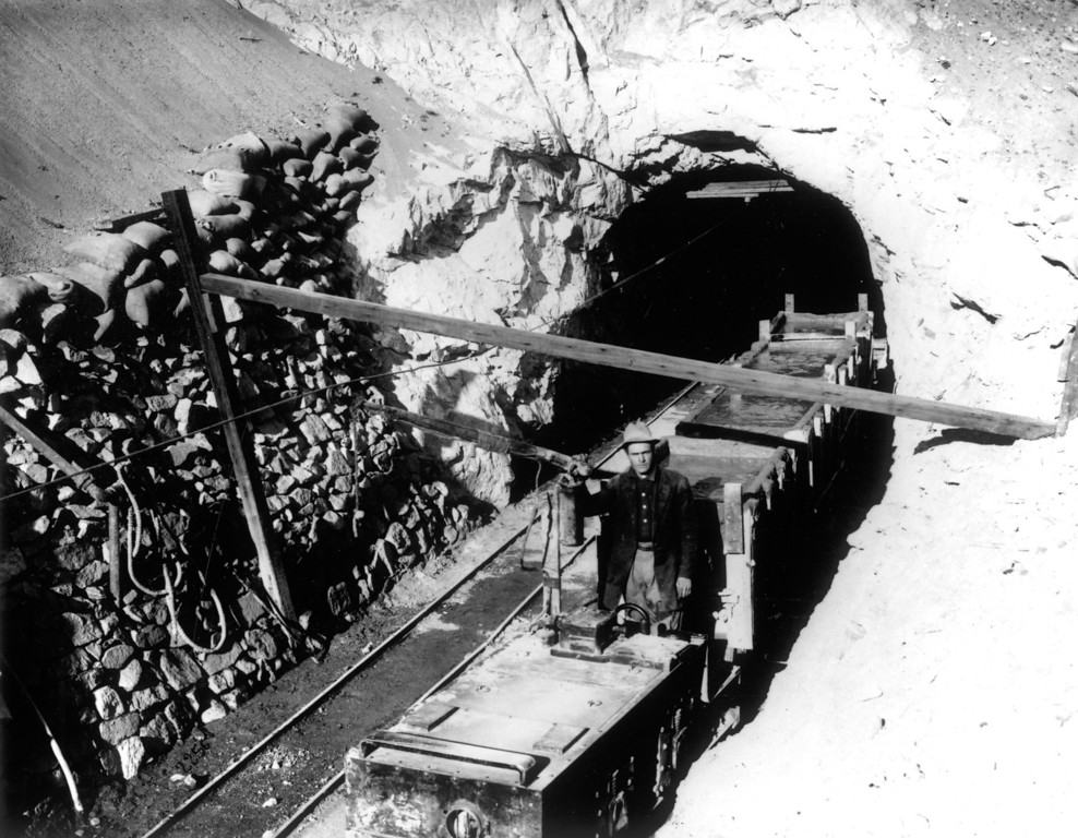 . A mine train exits one of 142 tunnels along the aqueduct route. The total length of these tunnels, which were drilled in mostly rugged mountain terrain, is 53 miles.   (Los Angeles Daily News undated file photo)