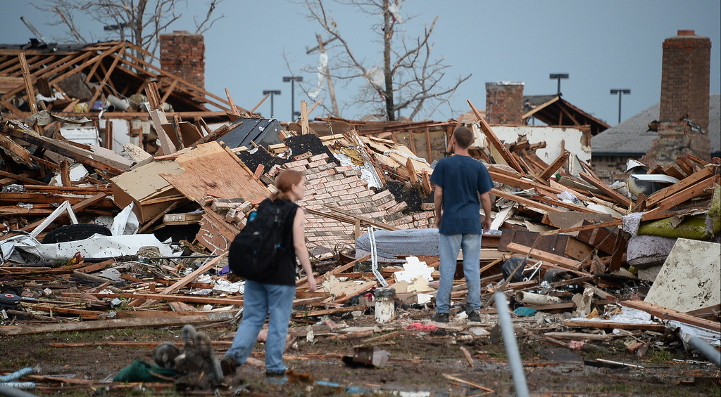 . A couple look for their home among the destroyed buildings. 
