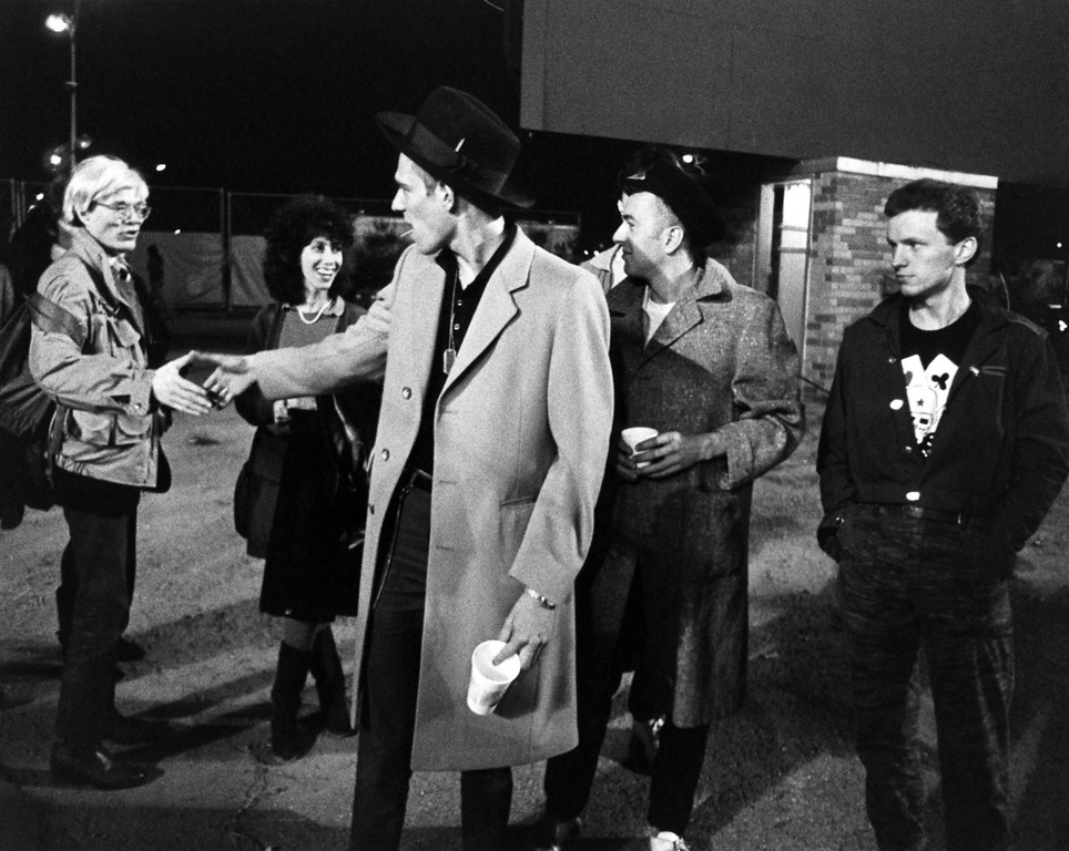 . In this 1982 image released by Epic/Legacy Records, artist Andy Warhol, left, and publicist Susan Blond, second left, are shown backstage with members of The Clash, Paul Simonon, center, Joe Strummer and Terry Chimes, right, at Shea Stadium in New York. (AP Photo/Epic/Legacy Records, Bob Gruen)