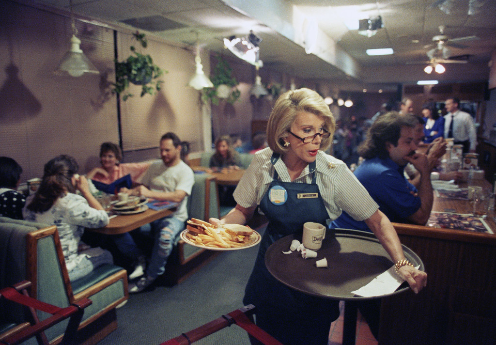 . Talk show host Joan Rivers works a job as a waitress at a Denny\'s restaurant in West Palm Beach, Fla., Feb. 21, 1992. Rivers is switching jobs with Rhonda Denton who works at the restaurant and who will take over River\'s job in New York on a program which will air on March 4. (AP Photo/Ray Fairall)
