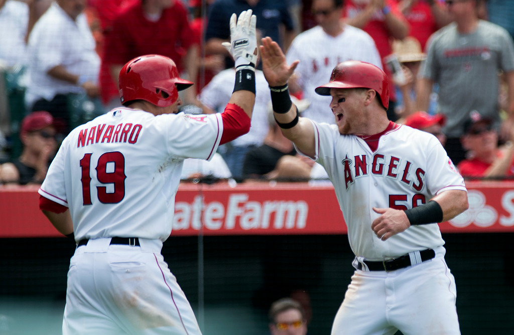 . Angels\' Kole Calhoun (#56) and Efren Navarro ((#19) celebrate after scoring as they play the Minnesota Twins at Angel Stadium in Anaheim on Thursday June 26, 2014. The Angels beat the Minnesota Twins 6-4. (Photo by Keith Durflinger/Whittier Daily News)