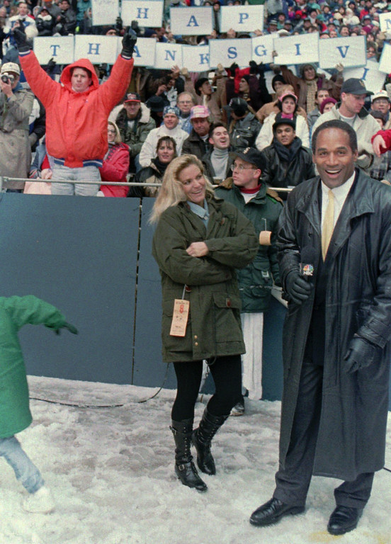 . O.J. Simpson wears gloves as he stands with his wife Nicole on the sidelines of Texas Stadium in Irving, Texas, during the Thanksgiving Day game between the Dallas Cowboys and the Miami Dolphins Nov. 24, 1993.  A prosecutor accused O.J. Simpson of skipping his daily dose of arthritis medicine so his hands would swell, making them too large to fit into gloves linked to murder, a courtroom transcript showed Thursday, June 22, 1995. (AP Photo/Ron Heflin)