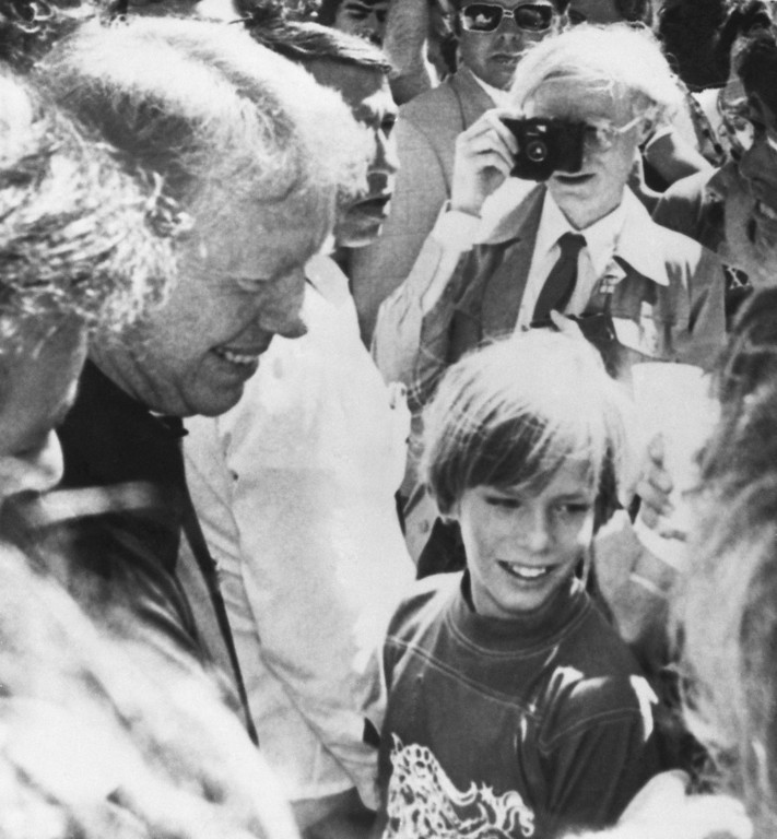 . Jimmy Carter (left) shakes hands at a picnic given by the Capricorn Record Co., August 20, 1976 in Macon, Ga. With a camera to his eye in the background is pop artist Andy Warhol who will take the Democratic presidential nominee\'s picture at his home today. Two hundred copies of the photo will be sold at $2,000 a piece, with proceeds going to the National Democratic Committee. (AP Photo)