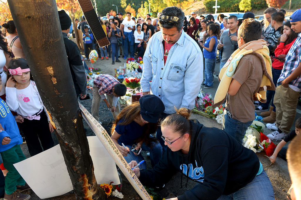 . Griselda Perez, left, Bobby Nelson, standing, and Tiffanie Rayas, lower right, sign a memorial for Paul Walker and Roger Rodas, Sunday, December 1, 2013, at the scene of their fatal crash site on Hercules Street near Kelly Johnson Parkway in Valencia. (Photo by Michael Owen Baker/L.A. Daily News)