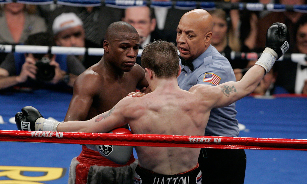 . Floyd Mayweather Jr., left, is separated from Ricky Hatton, of Great Britain, by referee Joe Cortez during their WBC welterweight boxing title fight at the MGM Grand hotel-casino in Las Vegas, Saturday, Dec. 8, 2007. Mayweather won by knockout in the 10th round. (AP Photo/Reed Saxon)